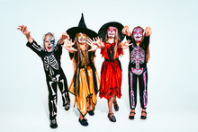 Kids Or Teens Like Witches And Vampires With Bones And Glitter On White Background. Caucasian Models Looks Scary And Playful. Halloween, Black Friday, Sales, Autumn Holidays Concept. The Night Of Fear