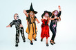 canvas print picture Kids or teens like witches and vampires with bones and glitter on white background. Caucasian models looks scary and playful. Halloween, black friday, sales, autumn holidays concept. The night of fear
