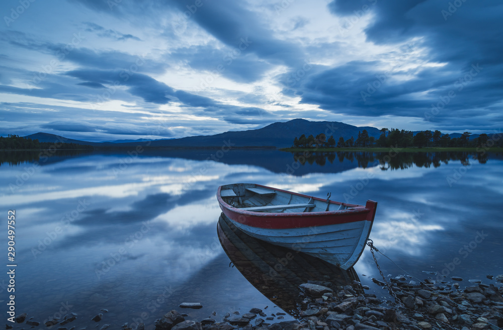 Fototapeta Old rowing boat at the rocky shore of a lake on a cloudy evening. Jamtland, Sweden.