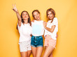 canvas print picture - Three young beautiful smiling hipster girls in trendy summer clothes. Sexy carefree women posing near yellow wall in studio. Positive models going crazy and having fun.They show tongue