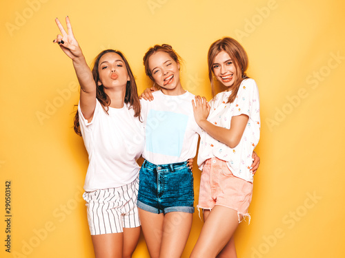 Three young beautiful smiling hipster girls in trendy summer clothes Tableau sur Toile