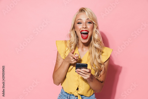 Image of beautiful woman laughing and holding cellphone Fototapet