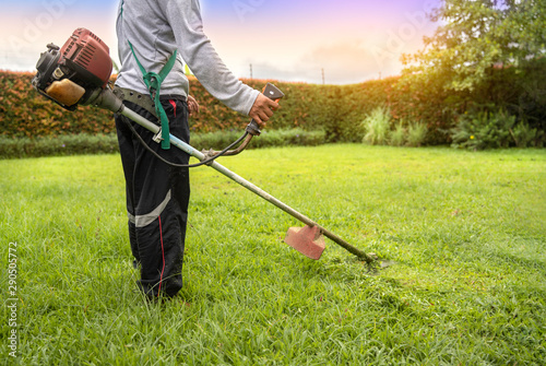 Poster Jardin A man holding grass trimmer. Worker mowing lawn with garden trimmer rotating left and right.