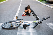 Kid Hurts His Leg After Falling Off His Bicycle. Child Is Learning To Ride A Bike. Boy In The Street Ground With A Knee Injury Screaming After Falling Off To His Bicycle.