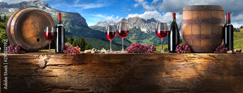 Acrylic Prints Wine red wine on an old wood with a landscape background