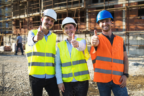 Obraz Three construction workers having meeting,pose for the photographer,stock photo - fototapety do salonu