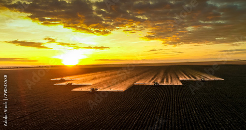 Photo Spraying pesticides and fertilizers on sunset cotton crop