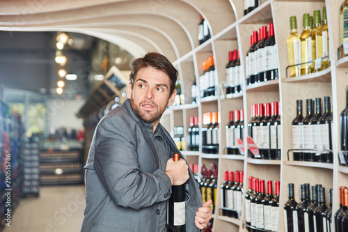 Cuadros en Lienzo  Mann steckt eine Flasche Wein in seine Jacke
