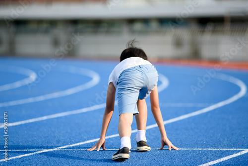 Obraz Young boy running on blue track - fototapety do salonu