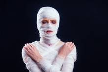 Glamorous Mummy Woman In Bandages All Over Her Body In Studio Black Background. Halloween Party Or Plastic Surgery Victim Concept
