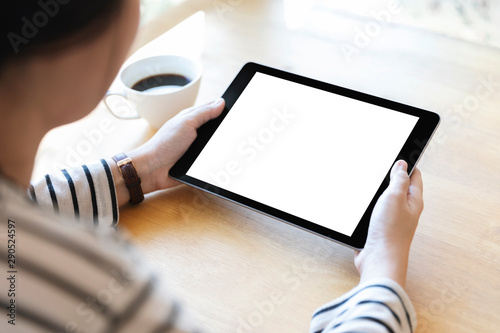 Obraz Hands holding black digital tablet pc with white blank screen on wooden table background in cafe. - fototapety do salonu