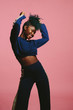 canvas print picture Cool young woman dancing in a blue sweatshirt  with arms up