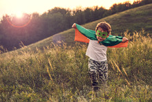 Little Boy Playing A Superhero. Kid In An Superhero's Costume. Happy Child Runs To Meet The Photographer.