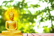 Leinwanddruck Bild Buddha statue with aura on yellow sky background