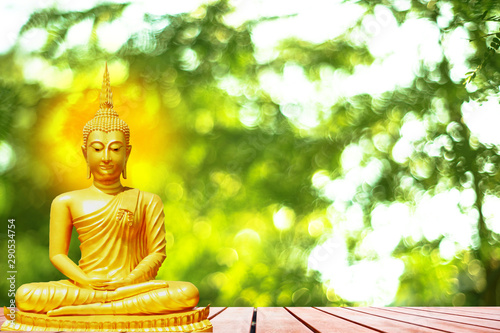 Leinwanddruck Bild - Richman Photo : Buddha statue with aura on yellow sky background