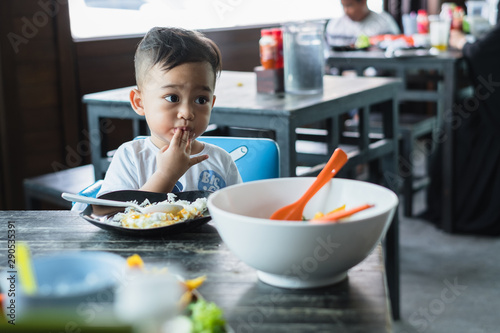 Little Thai baby boy 1 year old eating rice with fried egg with hand by himself sitting on baby chair in the restaurant Canvas Print