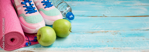 Fototapeta Pink yoga mat, sport shoes, bottle of water and apples on blue wooden background. Sport, healthy lifestyle, yoga concept. Female sport equipment. Copy space obraz