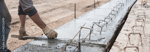 Fotomural Construction worker is leveling concrete pavement at road construction site