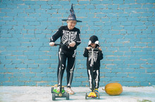 Elderly Grandmother Rides Scooter With Pretty Bright Blonde Grandson. Grandmother And Grandson Play Fun Together. Skeleton Costume, Pumpkin And Witch Hat. Halloween Eve