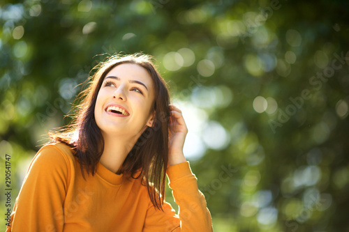 Fotografía Close up happy young woman laughing in park with hand in hair