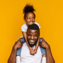 Cheerful African Dad Riding His Cute Little Daughter On Shoulders