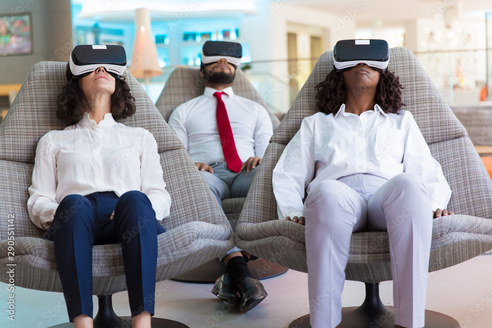 Fototapeta Multiethnic colleagues in VR glasses watching content together. Business man and women wearing virtual reality headsets, sitting in motion chairs. Teamwork or virtual content concept
