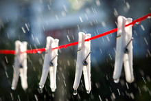 White Clothes Pegs On A Red Washing Line In The Rain