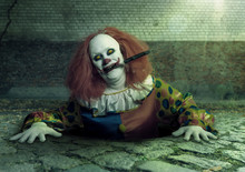A Killer Clown With A Knife In The Mouth Rising From The Sewer