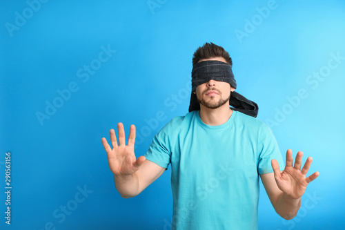 Obraz na plátně Man with black blindfold on blue background, space for text