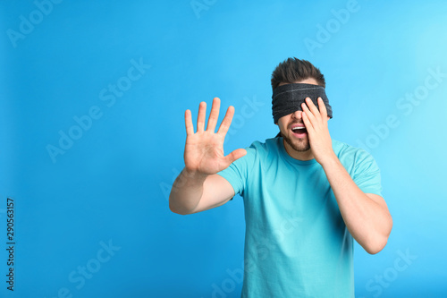 Fotografie, Obraz Man with black blindfold on blue background, space for text