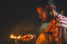 A Man Wearing Beads Is Holding A Flame To A Candle Holder.