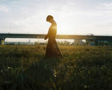 A Woman Standing In A Field Wi...