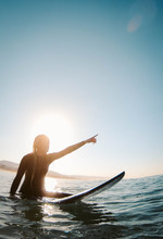 A Young Woman Straddles A Surfboard In The Ocean.