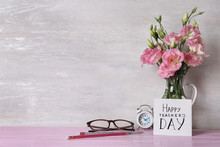 Card With Inscription HAPPY TEACHER'S DAY And Vase Of Flowers On Pink Table Against Light Wall, Space For Text