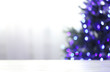 canvas print picture Empty table and blurred fir tree with violet Christmas lights on background, bokeh effect. Space for design