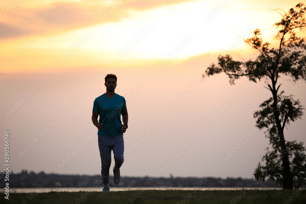 Fototapeta Young man running outdoors in evening. Space for text