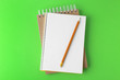 canvas print picture - Notebooks with pencil on light green background, top view