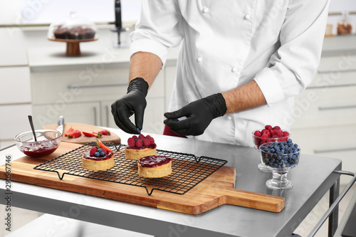 Male pastry chef preparing desserts at table in kitchen, closeup Poster Mural XXL