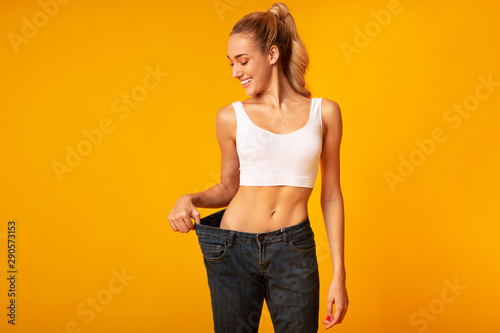 Fototapeta Young Woman In Oversize Jeans Posing, Yellow Background, Studio obraz