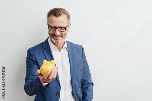 Fototapeta Successful businessman looking at his piggy bank obraz