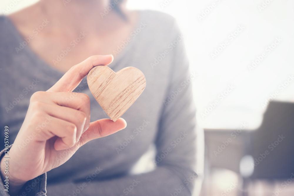 Fototapety, obrazy: Female hand holding a wood heart shape, copy space.