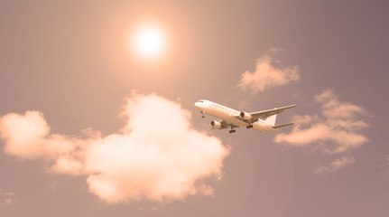 Passenger plane against the sky and white clouds. Evening sunset.