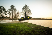 Man Teen Boy Riding A Personal Watercraft And Jumping Over A Peninsula At Sunset On A Small Lake Pond