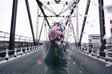 Photography Of Woman Between Road While Holding Flower