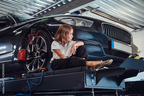 Fotografía  Pretty kid is sitting near new shiny car while posing for photographer
