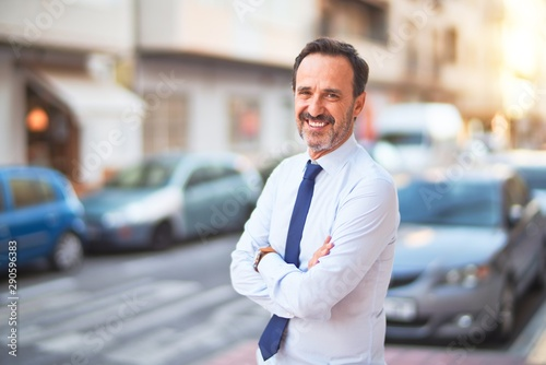 obraz PCV Middle age handsome businessman wearing shirt and tie standing on the street smiling