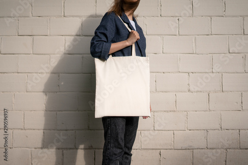 Fototapety, obrazy: Urban mockup of tote bag. Girl holding white cotton tote bag on a brick wall background. Template can be used for you design