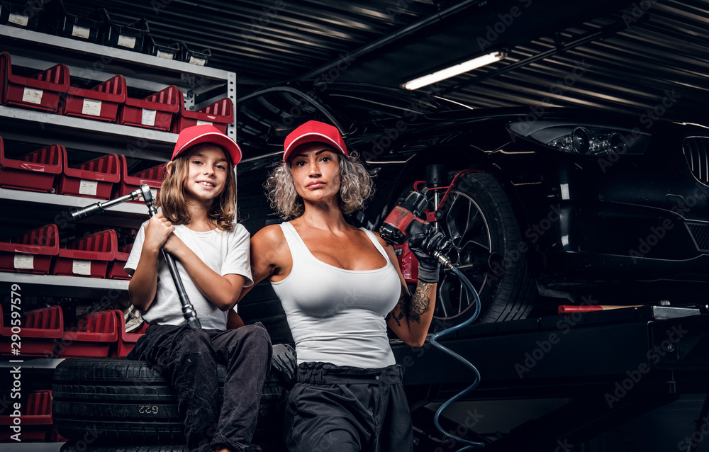 Fototapeta Experienced serious woman and her little helper are posing for photographer at dark auto service as great team.