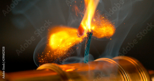 MACRO, DOF: Burning match lights up the short fuse of a vintage brass cannon Tablou Canvas