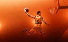 Professional Basketball Player On Basketball Court In Action With The Ball. Slam Dunk. Red Floodlit Background